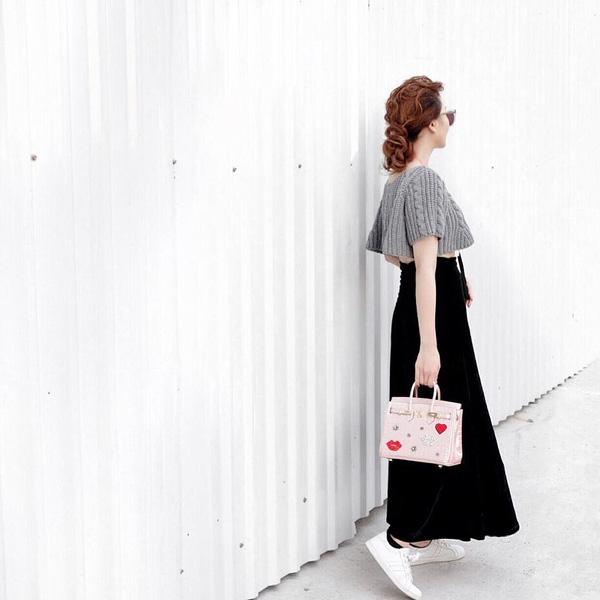 Yến Trang kết hợp chân váy dài thướt tha cùng áo hở eo gợi cảm. Nữ ca sĩ không quên làm điệu cho tổng thể bằng chiếc túi xách màu hồng hợp xu hướng.