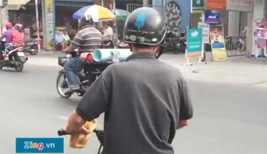 Người đàn ông chạy xe máy đến và lấy 2 ổ một lúc. (Ảnh cắt từ clip Zing.vn)