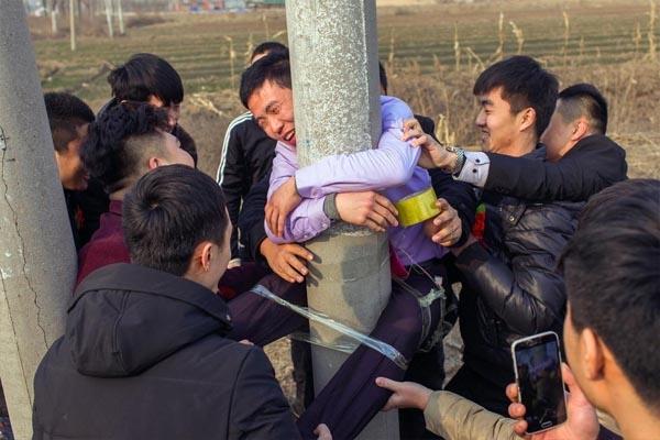 Được biết, anh chàng họ Trương, đang trên đường đi đón dâu thì bất ngờ bị bạn bè thân thiết kéo xuống xe và dùng băng dính chuẩn bị sẵn dính trói lên cột điện. Sau đó, bạn bè anh đồng loạt chụp ảnh và gửi cho vợ của anh chàng xem.