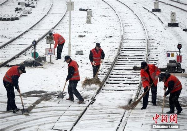 Công nhân đường sắt ở Giang Tây quét dọn tuyết chờ đoàn tàu vào ga.