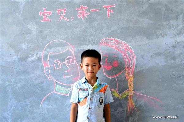 Cậu bé Song Junyi cười thích thú với bố mẹ mình.