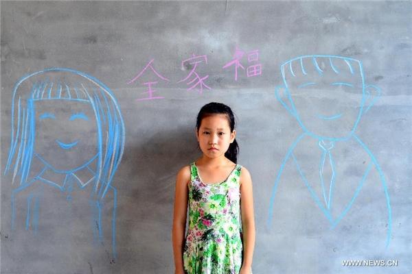 Xu Kexin khoe các bức vẽ về cha mẹ trên một bảng đen.