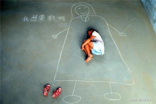 Xindi ngủ trong vòng tay của mẹ – được vẽ bằng những nét ngây thơ và nguệch ngoạc trên mặt đất.