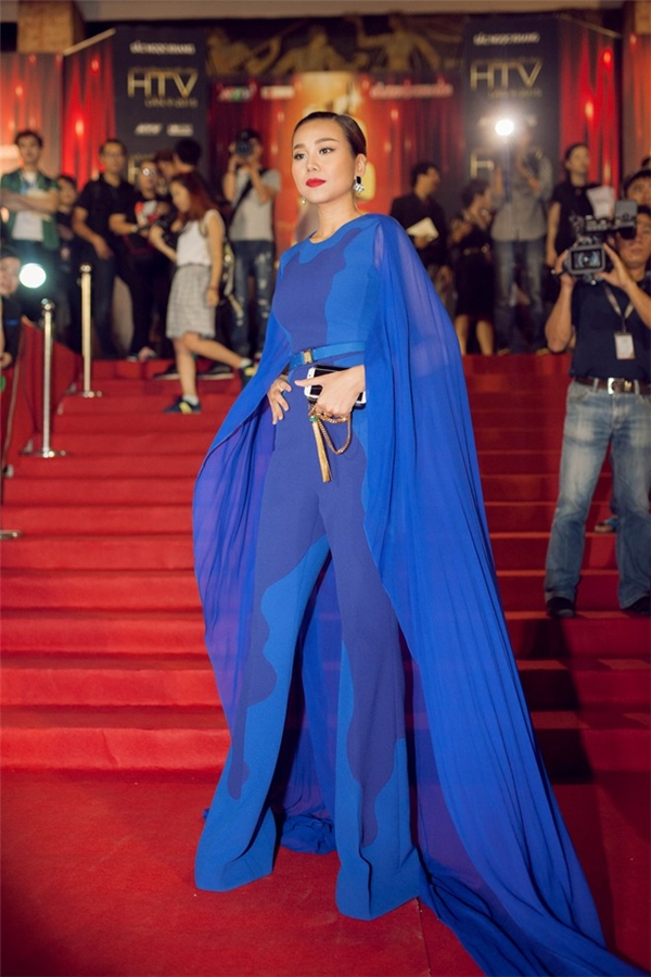 Bộ jumpsuit kết hợp áo choàng cape bằng voan lụa có tông xanh cobant trẻ trung trở thành một trong những dấu ấn của Thanh Hằng trên thảm đỏ của năm 2015.