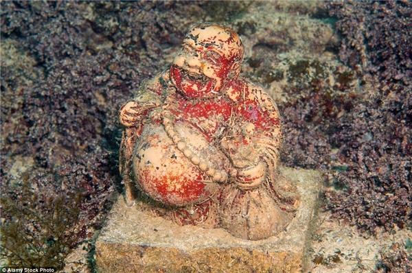 Tượng Phật cười rạng rỡ nằm trên một tấm thảm được tạo thànhbởi những sợi rong biển màu tía.(Ảnh: Daily Mail)