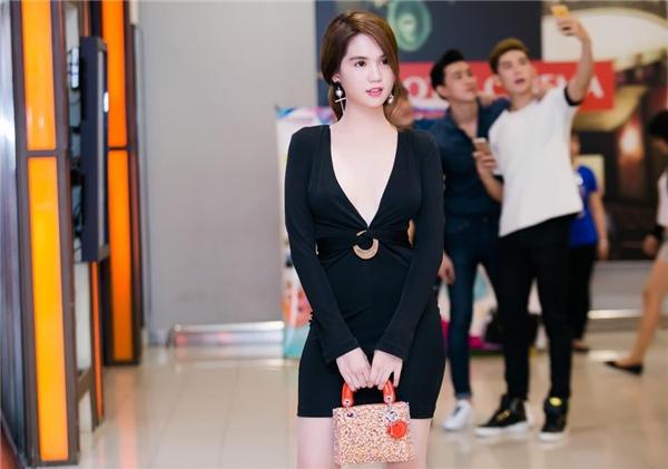 Diện kiểu váy đen ôm sát đơn giản, Ngọc Trinh không quên thêm một chút gợi cảm bằng đường xẻ ngực sâu hun hút. Kết hợp cùng bộ trang phục là chiếc túi xách Lady Dior có giá gần 100 triệu đồng.