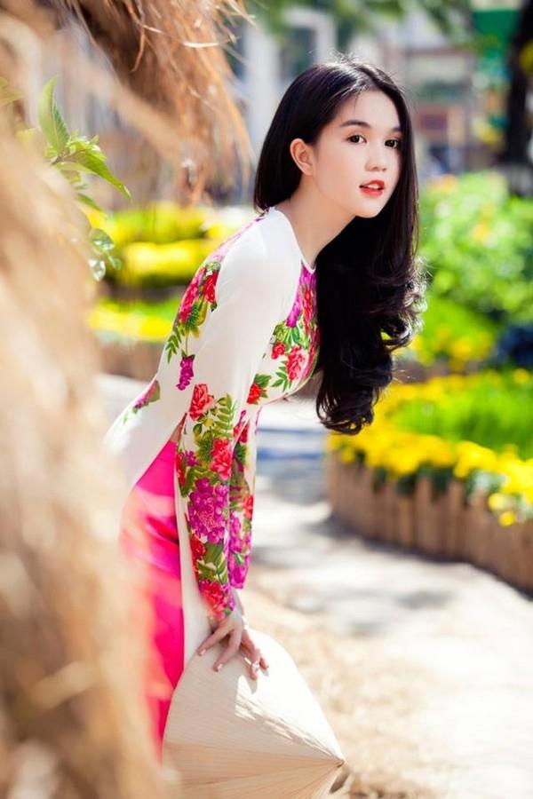 Họa tiết hoa lá phủ trên nền sắc trắng tinh khôi, nhẹ nhàng từng trở thành mốt áo dài khá được ưa chuộng. Ngọc Trinh tạo nên sự đồng điệu cho tổng thể với sắc hồng cánh sen thẫm ngọt ngào, điệu đà.