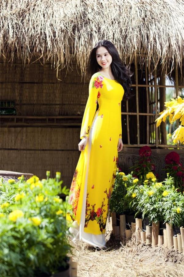 Sắc vàng của hoa cúc như sưởi ấm cả khung trời mùa xuân đã được gom trọn vào chiếc áo dài cổ truyền mà Ngọc Trinh diện. Những hoa đào mỏng manh được khéo léo điểm xuyết như sự giao hòa giữa mùa xuân hai miền.