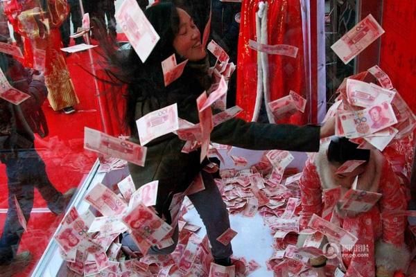 """Những người tham gia trò chơi sẽ chui vào một hộp kính chứa đầy những tờ tiền giấy mệnh giá 100 tệ (tương đương 340 nghìn đồng), sau đó mặc sức """"vơ vét"""" trong vòng 1 phút."""