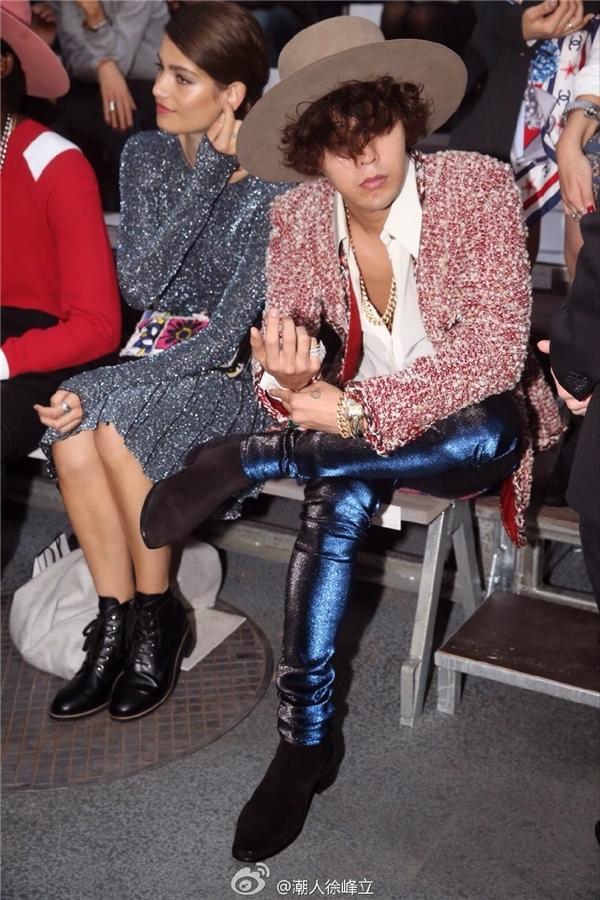 Đúng với chủ đề womenswear, G-Dragon thể hiện sở thích ăn mặc theo phong cách unisex thường thấy khi kết hợp áo khoác tweed, quần ánh kim xanh và ankle boots.