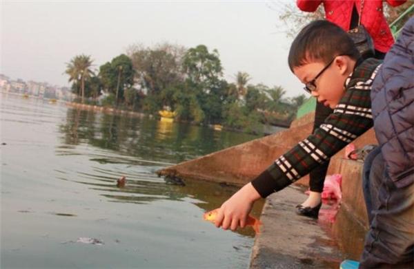 Người dân nô nức thả cá chép vào ngày đưa ông Táo về trời. Ảnh: Internet