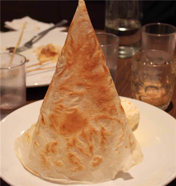 Đây là một món bánh được phục vụ trong các quán ăn Ấn Độ. Bánh mỏng nhưng giòn, được đầu bếp khéo léo cuộn lại trông như một chiếc nón khá sinh động. Khi ăn, bạn sẽ cảm nhận được vị béo béo mằn mặn của bơ, một chút ngòn ngọt của nước đường dẻo, nhâm nhi cùng một cốc trà sữa teh tarik nóng thì tuyệt vời.(Ảnh: Internet)