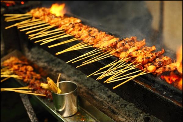 """Thịt nướng satay cũng là một trong những món """"nhất định phải ăn"""" khi đến Malaysia. Trên đường phố hay trong nhà hàng, quán ăn, bạn rất dễ dàng mua vài xiên thịt nướng này để nhâm nhi. Thịt gà mềm thấm đẫm vị cay nồng của sa tế, còn nóng hổi được ăn cùng sốt đậu phộng, hương vị không thể chê vào đâu được.(Ảnh: Internet)"""