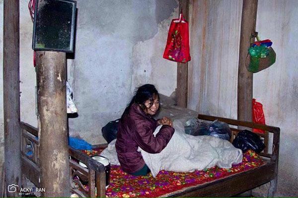 Bà Teo một mình trên chiếc giường trong căn nhà dột nát, xập xệ.