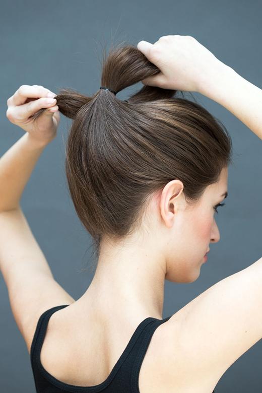 Bước 2: Tách đôi phần tóc trên đầu ra để luồn chiếc đuôi ngựa vào phân nửa. (Ảnh: Stephanie Stanley)
