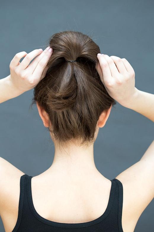 Bước 3: Dùng cả 2 tay để xòe phần búi tóc bên trên ra thành hình tròn. Dùng kẹp tăm giấu phần đuôi tóc vào chân búi tóc. (Ảnh: Stephanie Stanley)