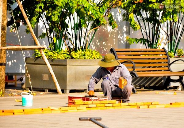 Một công nhân đang xây viền xung quanh cho một phần tiểu cảnh của đường hoa.
