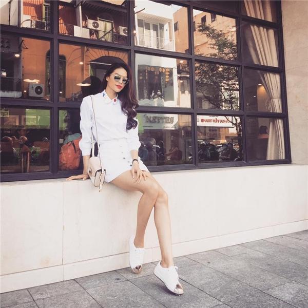 Cùng sử dụng sắc trắng, cách kết hợp giữa áo sơ mi cùng chân váy cài cúc giữa vừa mang hơi thở của thời trang nữ tính nhưng lại vừa phảng phất chút cá tính, bụi bặm. Những dáng váy có độ dài vừa phải luôn được Phạm Hương chọn diện trong những lần xuống phố.