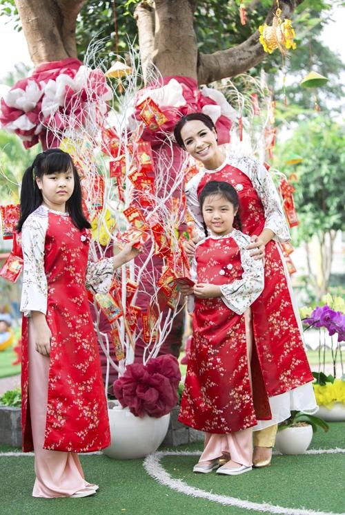 Thúy Hạnh cùng Suli và Suti diện áo dài đồng điệu với họa tiết hoa đào li ti làm điểm nhấn.
