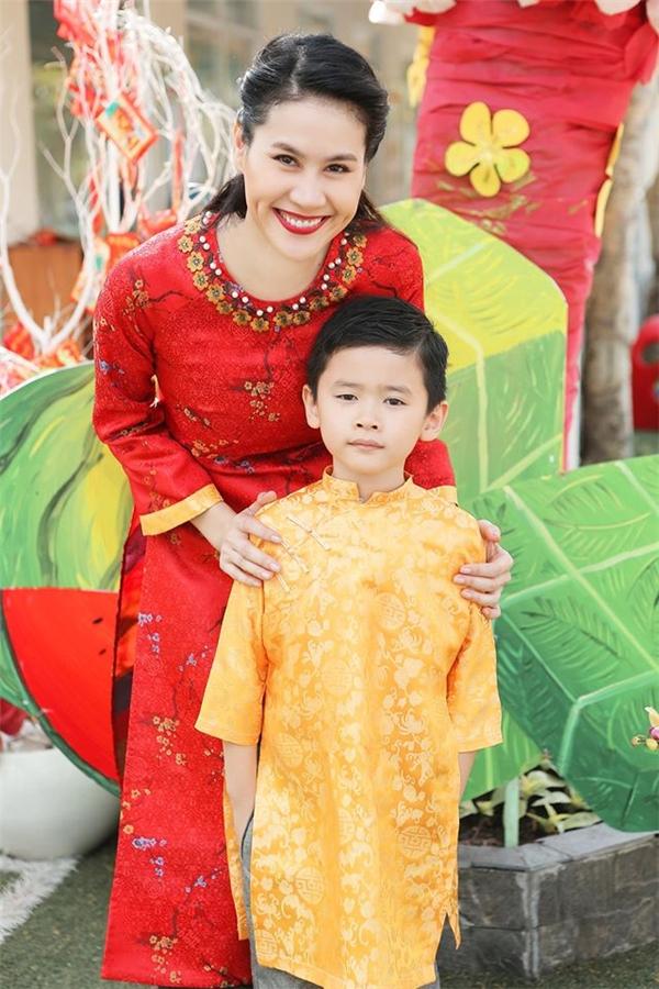 Thân Thúy Hà diện áo dài đỏ rực bên cạnh cậu con trai Duy Anh kháu khỉnh. Trong dịp tết năm nay, áo dài gấm gần như trở thành xu hướng được lựa chọn hàng đầu bởi sự sang trọng, đẳng cấp.