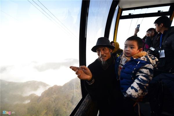 """Ông Hà Văn Khuyên (70 tuổi) và cháu ngoại Lê Trọng Hà (3 tuổi, sống tại phố Tuệ Tĩnh, thị trấn Sa Pa) là hai trong số những người đầu tiên lên """"nóc nhà Đông Dương"""" bằng cáp treo. Ông Khuyên tâm sự, trong đời từng hai lần leo bộ lên đỉnh Fansipan vào các năm 1972 và 1987. Năm 1987, ông là người dẫn đoàn Liên Xô lên đặt cột mốc 4 cạnh tại đây."""