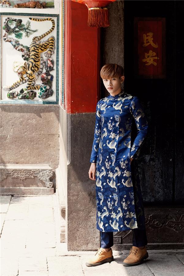 Chàng trai Dương Minh Tuấn chọn diện áo dài với tông xanh trầm mặc. Thiết kế tạo điểm nhấn bởi họa tiết rồng được in thoắt ẩn thoắt hiện. Đây cũng chính là loài vật biểu trưng cho sự thịnh vượng, phồn vinh theo quen niệm của người Á đông.