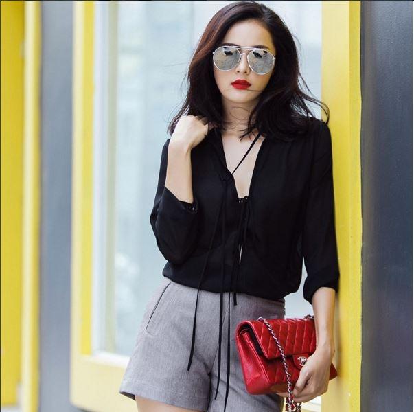 Sắc đen, xám kinh điển trở nên lạ mắt qua combo: quần short kết hợp áo xẻ ngực sâu. Một chiếc túi xách màu đỏ, một chiếc kính mặt gương đi kèm - thế là quá đủ để các cô nàng du xuân.