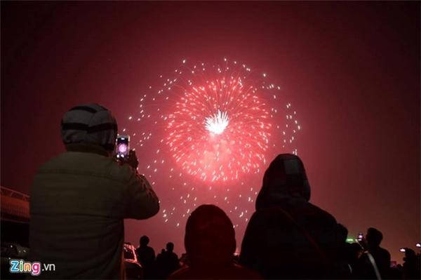 Dùng điện thoại ghi lại hình ảnh pháo hoa bừng sáng trên bầu trời. Ảnh: Zing.vn