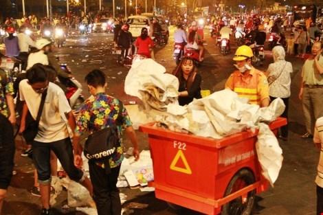 Các bạn trẻ nán lại dọn dẹp rác ngay sau khi màn bắn pháo hoa kết thúc. Ảnh: Internet