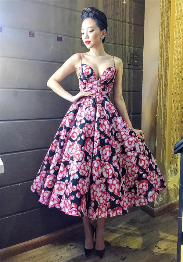 Tóc Tiên gợi cảm với dáng váy hai dây xẻ ngực sâu hút. Lấy nền đen làm chủ đạo, những họa tiết hoa to bản màu đỏ, trắng vừa nổi bật vừa hài hòa tạo nên bức tranh ngọt ngào cho quý cô trong ngày đầu năm mới.