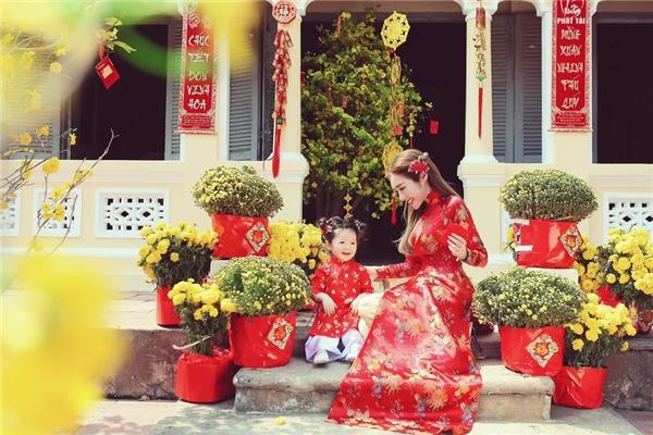 Trước đó, hai mẹ con hot girl đình đám khiến người hâm mộ vô cùng thích thú khi diện áo dài đỏ trên nền vải gấm, lụa bóng kết hợp những họa tiết thêu tay, in chìm màu vàng đồng nổi bật. Không gian tràn ngập hoa lá khoe sắc như thu gọn cả mùa xuân phương Nam vào trong khung ảnh.