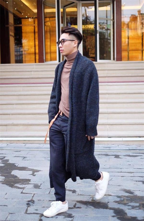 Chiếc áo khoác dài ấn tượng được Hoàng Ku kết hợp khéo léo cùng áo cổ lọ, quần âu, giày thể thao với những gam màu nhẹ nhàng, trầm ấm.