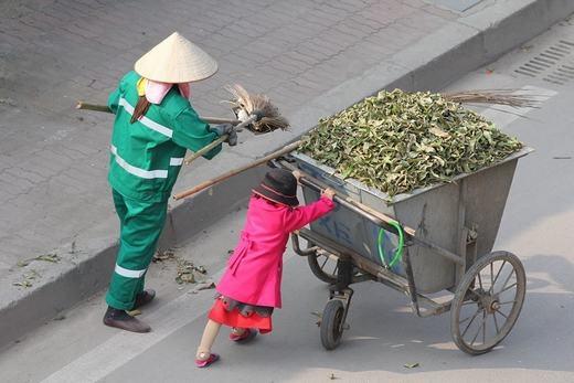 Hình ảnh em bé mặc đẹp, mặt tươi rói giúp mẹ là công nhân lao công khiến nhiều người xúc động.
