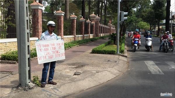 Người cha với tấm biển xin lỗi vì đã vi phạm luật giao thông gây xôn xao sáng 12/2. Ảnh: Lê Hồng Thảo