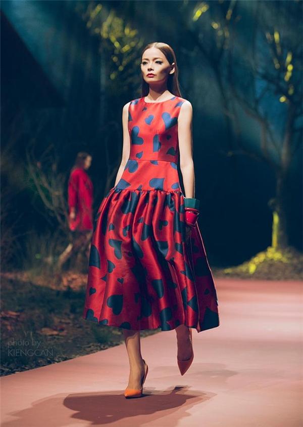 Phom váy xòe kinh điển trở nên mới lạ hơn nhờ cấu trúc phân tầng lạ mắt. Họa tiết tim màu sẫm tương phản với nền đỏ nổi bật, thu hút.