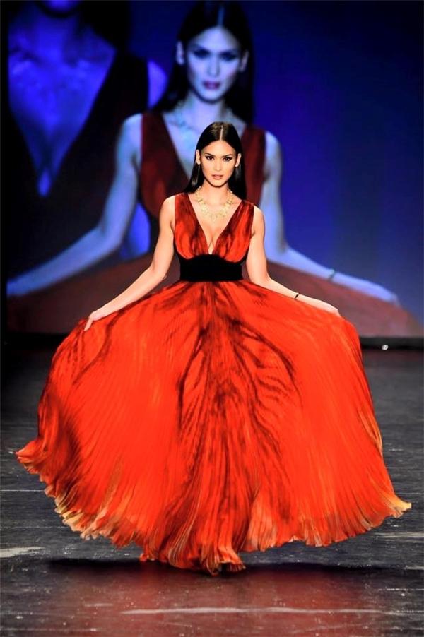 Trên sàn diễn, Pia diện chiếc váy đỏ xẻ ngực sâu hút gợi cảm. Thiết kế được thực hiện trên nền chất liệu voan lụa mềm mại với những đường dập li tinh tế. Từng bước di chuyển của Pia giúp chiếc váy trở nên mềm mại, thanh thoát hơn. Đây là thiết kế của nhà mốt Carmen Marc Valvo.