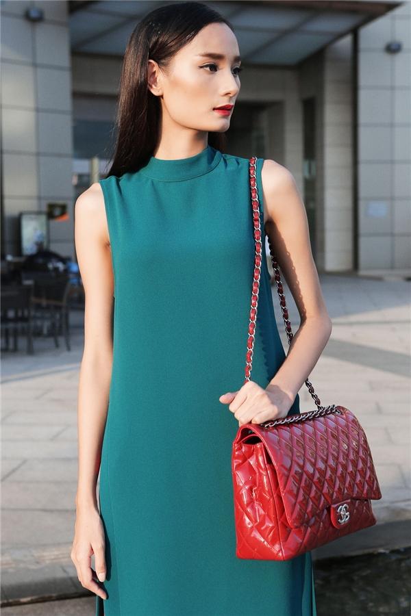 Sự tương phản càng được đẩy lên mạnh mẽ khi nữ người mẫu kết hợp trang phục cùng chiếc túi màu đỏ sang trọng, bắt mắt của Chanel.