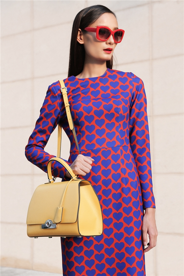 Nữ người mẫu khoe vóc dáng thanh mảnh trong dáng váy bodycon ôm sát thanh lịch, sang trọng. Họa tiết tim được trải đều khắp nền vải tạo nên hiệu ứng thị giác bắt mắt. Kết hợp với bộ váy là chiếc túi màu vàng nhẹ nhàng của Moynat - một thương hiệu hàng đầu của Pháp có mặt trước cả Hermes, LV…