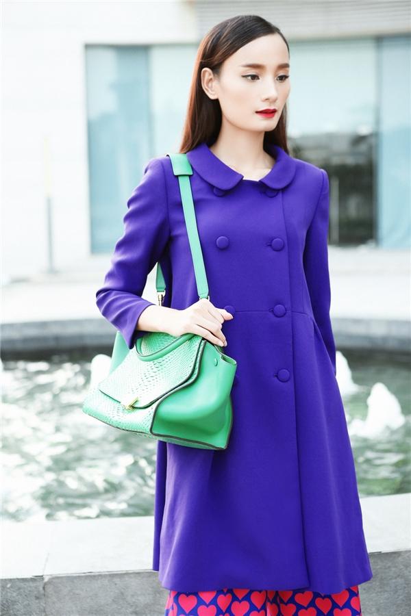Chiếc túi xách màu xanh càng giúp tổng thể trở nên màu sắc, thu hút. Đây là thiết kế của thương hiệu hàng đầu thế giới Celin.