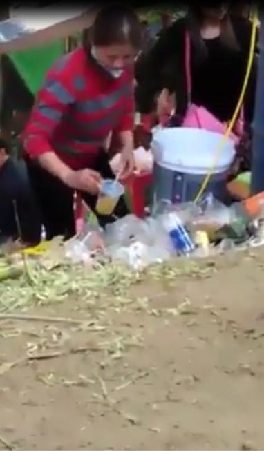 Hình ảnh người phụ nữ nhặt đá bẩn, cốc qua sử dụng để bán nước cho khách gây bức xúc trong cộng đồng mạng. Ảnh: Cắt từ clip