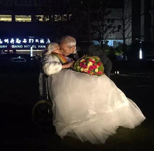 Nụ hôn nồng cháy trước tòa cao ốc rực rỡ ánh đèn LED minh chứng cho tình cảm lâu bền của đôi vợ chồng. (Ảnh: Internet)