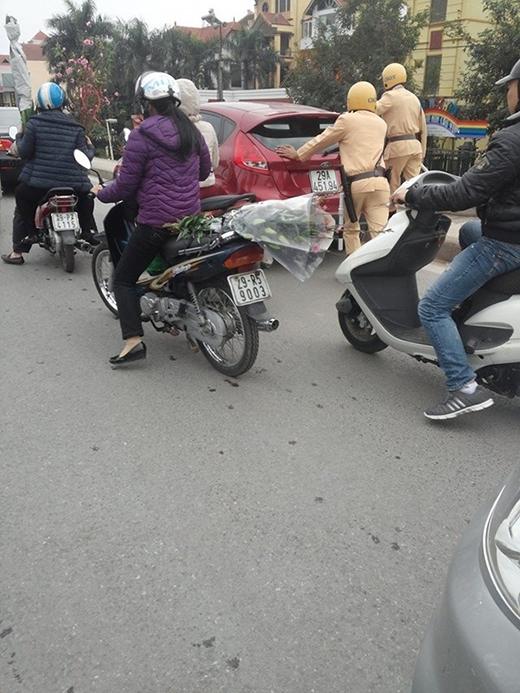 Ngày 29 Tết, một chiếc ô tô chết máy trên đường Âu Cơ, Hà Nội, được 2 anh cảnh sát giúp đẩy đi để làm thông thoáng cho đường phố. (Ảnh: Internet)