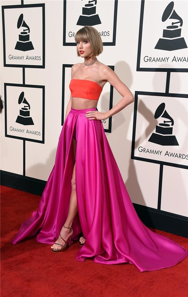 Taylor Swift gợi cảm, táo bạo với áo quâyngực cùng chân váy xòe rộng, xẻ tà sâu hun hút. Tổng thể trở nên bắt mắt hơn nhờ sự kết hợp giữa hai tông màu hồng, cam nổi bật.