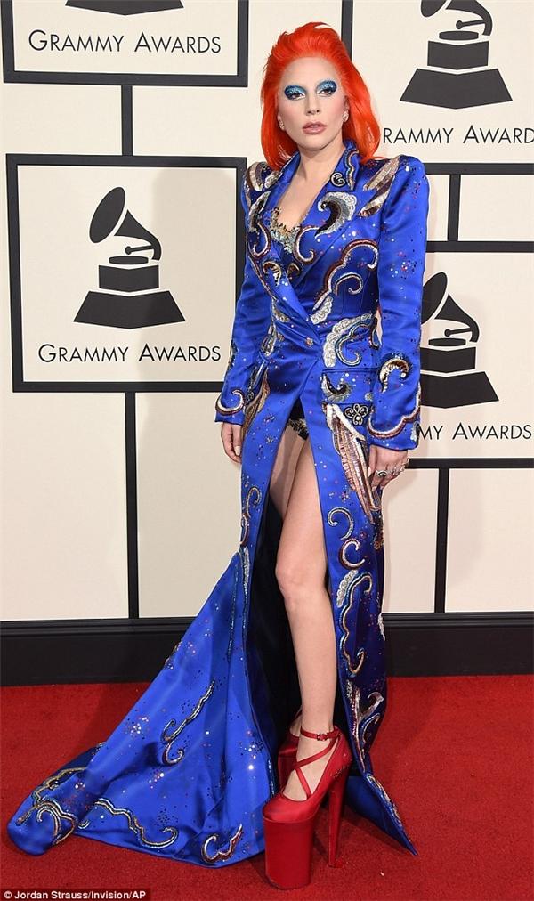 """Lady Gaga không hề kém cạnh khi diện bộ váy màu xanh cobalt trẻ trung với loạt họa tiết thêu tay, đính kết kì công. Nữ ca sĩ vẫn trung thành với vẻ ngoài """"dị biệt"""" thường thấy. Kết hợp cùng bộ trang phục là đôi giày cao gót """"khủng""""màu đỏ tương phản."""