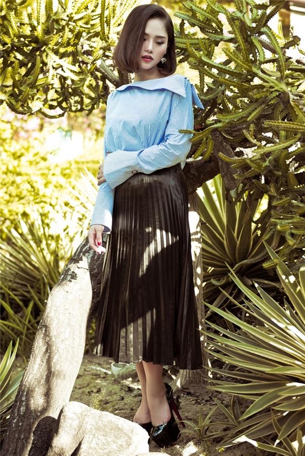 Diện chân váy xếp li điệu đà, nữ diễn viên Em là bà nội của anh khéo léo tạo nên nét chấm phá thú vị với áo sơ mi cổ thuyền tay loecó tông xanh thiên thanh dịu mát, trẻ trung.