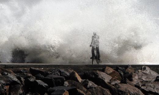 Một người đàn ông bị sóng lớn tạt qua tại một cảng cá ở Chennai, Ấn Độ. (Ảnh: Reuters)