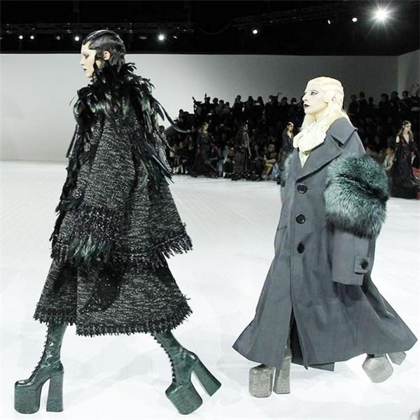 """Lady Gaga diện áo khoác măng tô dáng dài to sụ kết hợp khăn lông trên nền những tông màu trầm, ấm đặc trưng của mùa thời trang Thu - Đông. Kết hợp cùng bộ trang phục là đôi giày cao lêu khêu hơn 20cm. Tuy nhiên trong hậu trường của show diễn, Lady Gaga đã """"phàn nàn"""" với Marc Jacobs rằng: """"Nó không cao như tôi mong đợi"""". Còn việc đi giày cao như cà kheo của nữ ca sĩ cũng đã trở nên quá quen thuộc với khán giả."""