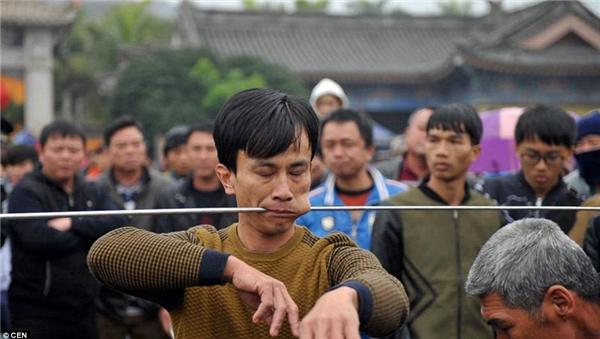 Người đàn ông dùng chiếc kim khổng lồ xuyên qua má tại lễ hội hàng năm được tổ chức trên núi Wenbi ở Hải Nam, Trung Quốc.