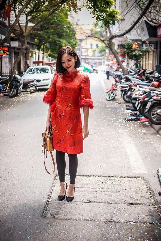 Tóc Tiên thanh lịch, đáng yêu với áo dài cách điệu trên nền vải gấm sang trọng cùng sắc đỏ nồng nàn, quyến rũ.
