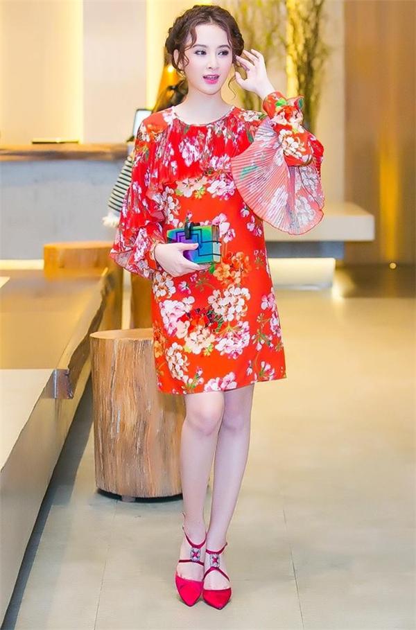 Sau hàng loạt váy áo gợi cảm, Angela Phương Trinh bất ngờ kín đáo, thanh lịch khi diện mẫu váy suông giấu đường cong. Thiết kế có tông màu cam nổi bật, thu hút kết hợp những họa tiết hoa lá đầy màu sắc đặc trưng của mùa thời trang Xuân - Hè.